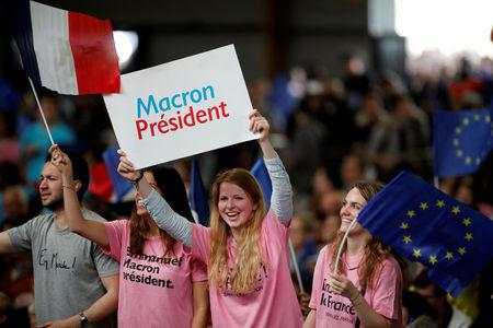 Supporters of Emmanuel Macron, head of the political movement En Marche !, or Onwards !, and candidate for the 2017 presidential election, hold placards and French and European flags before a campaign rally in Paris