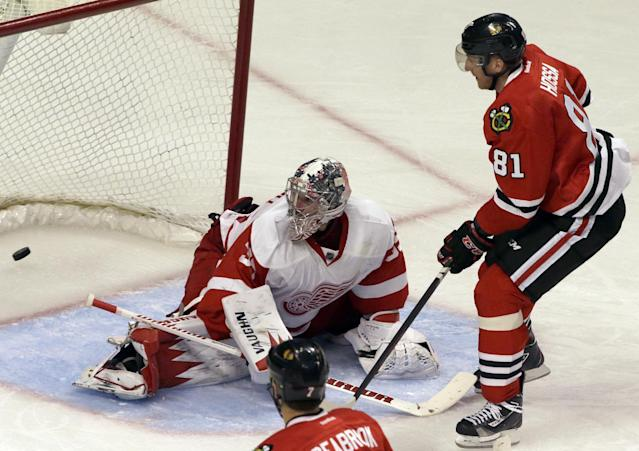 Chicago Blackhawks' Marian Hossa (81), right, scores against Detroit Red Wings goalie Jimmy Howard (35) during the third period of an NHL hockey game in Chicago, Sunday, March 16, 2014. The Blackhawks won 4-1. (AP Photo/Nam Y. Huh)