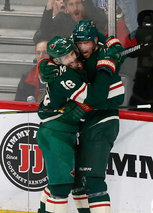 Minnesota Wild's Jason Zucker, left, and Eric Staal celebrate a goal by Staal against Chicago Blackhawks goalie Cam Ward during the second period of an NHL hockey game Thursday, Oct. 11, 2018, in St. Paul, Minn. Zucker also scored with seconds to play in the period to tie the game. (AP Photo/Jim Mone)