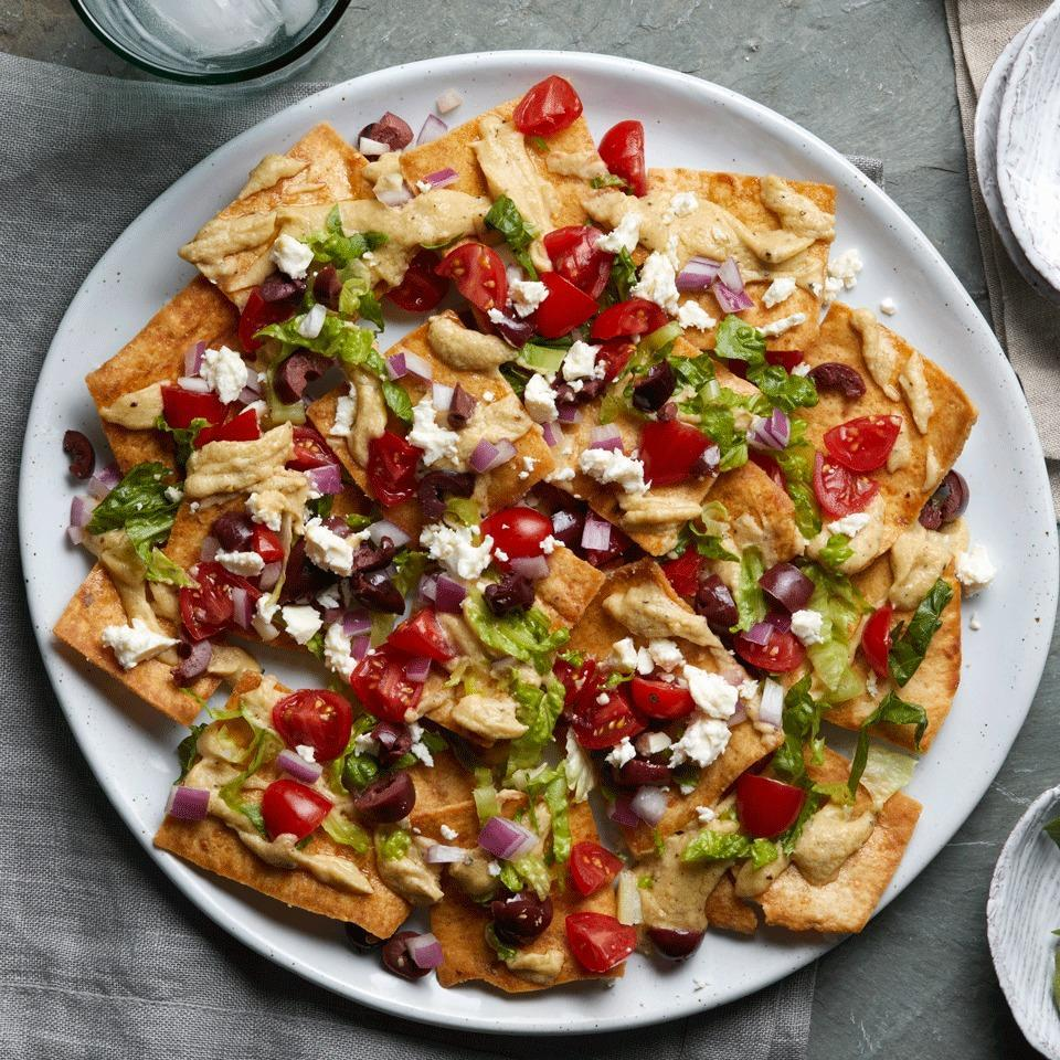 <p>This vegetarian nacho recipe is a fun combination of two favorites--nachos and Greek salad. It uses whole-grain pita chips instead of the tortilla chips used in traditional nacho recipes, and it's loaded with the classic fresh vegetables in Greek salad as well as creamy hummus and salty feta cheese. And it doesn't even need the oven! Easily doubled, this makes a great appetizer or light dinner.</p>