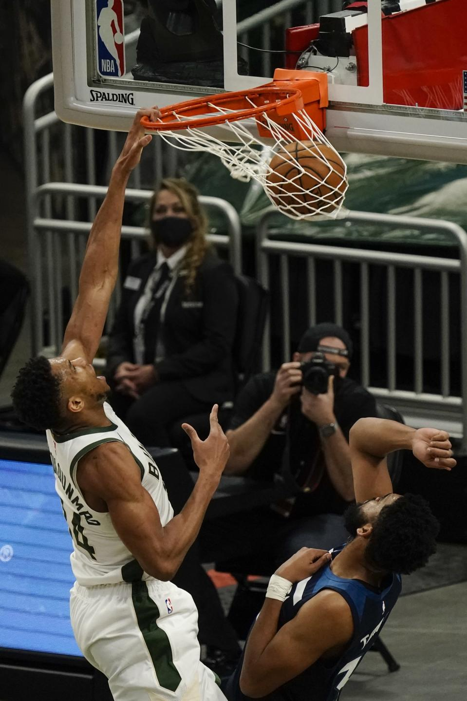 Milwaukee Bucks' Giannis Antetokounmpo dunks over Minnesota Timberwolves' Karl-Anthony Towns during the first half of an NBA basketball game Tuesday, Feb. 23, 2021, in Milwaukee. (AP Photo/Morry Gash)