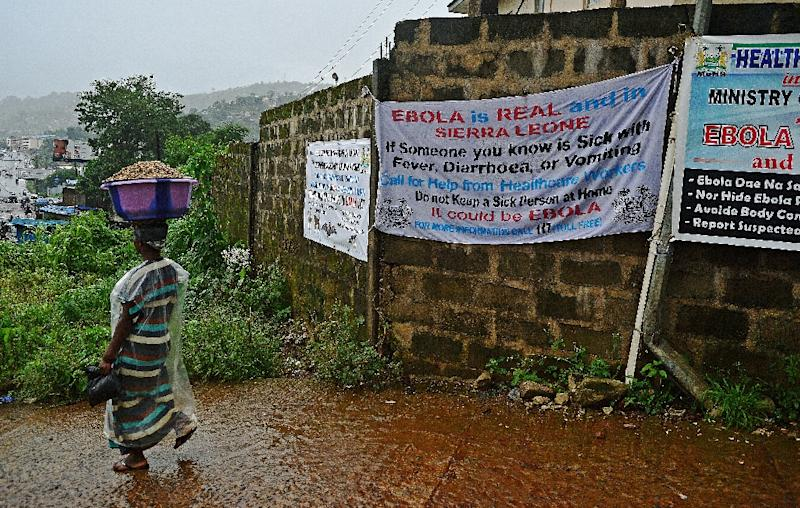 A woman walks past signs warning of Ebola in Freetown on August 13, 2014 (AFP Photo/Carl de Souza)
