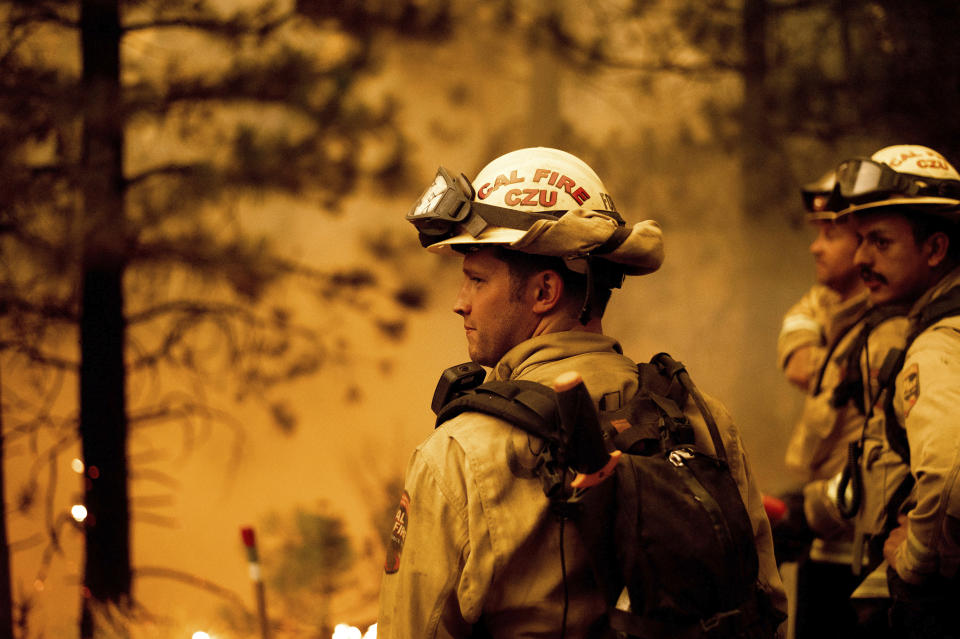 Firefighter Jesse Forbes monitors flames as his crew burns vegetation to stop the Dixie Fire from spreading near Prattville in Plumas County, Calif., on Friday, July 23, 2021. (AP Photo/Noah Berger)