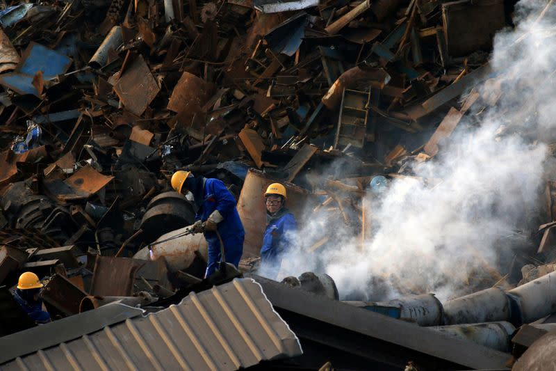 FILE PHOTO: Workers dismantle scrap metal at a steel plant in Huaian