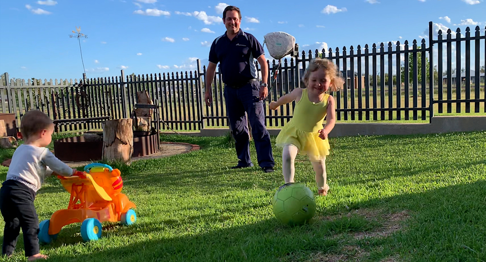Jason Smith playing with his two children in his backyard on the lawn.