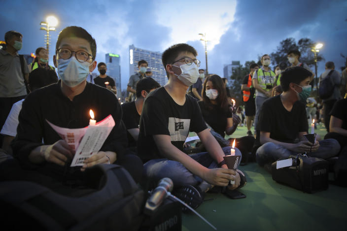 FILE - In this June 4, 2020, file photo, Hong Kong democracy activist Joshua Wong, center, holds a candle as he joins others for a vigil to remember the victims of the 1989 Tiananmen Square Massacre at Victoria Park in Causeway Bay, Hong Kong, despite applications for it being officially denied. Hong Kong authorities for the second year have banned the June 4 candlelight vigil to commemorate the bloody crackdown on pro-democracy protests in Beijing's Tiananmen Square in 1989, organizers said Thursday, May 27, 2021. (AP Photo/Kin Cheung)