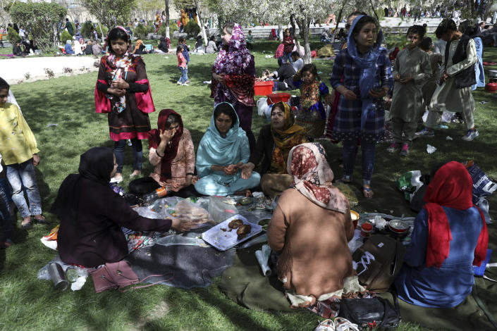 An Afghan family eat food at the park in Kabul, Afghanistan, Friday, April 9, 2021. (AP Photo/Rahmat Gul)