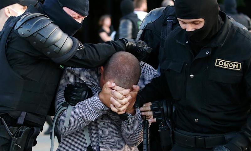 Police officers detain a participant in a protest in Belarus on Monday.