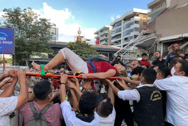 PHOTO: Rescue workers and local people carry a wounded person found in the debris of a collapsed building, in Izmir, Turkey, Oct. 30, 2020, after a strong earthquake in the Aegean Sea shook Turkey and Greece. (Ismail Gokmen/AP)
