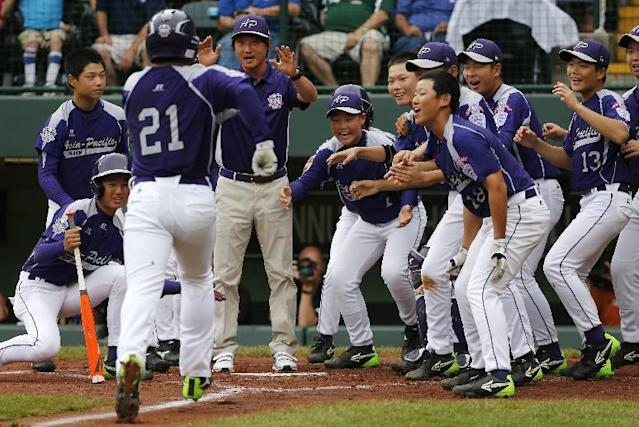 CORRECTS DATE AND YEAR TO AUG. 20, 2014 - Seoul's Hae Chan Choi (21) is greeted by teammates after hitting a two-run home run off Tokyo pitcher Takuma Takahashi in the second inning of a International semi-final baseball game against Tokyo at the Little League World Series tournament in South Williamsport, Pa., Wednesday, Aug. 20, 2014. (AP Photo/Gene J. Puskar)