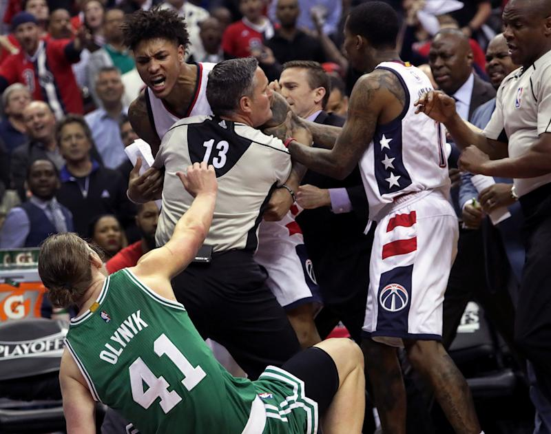 Wizards forward Kelly Oubre Jr., left, charges and knocks down Celtics center Kelly Olynyk on Thursday. (Getty Images)