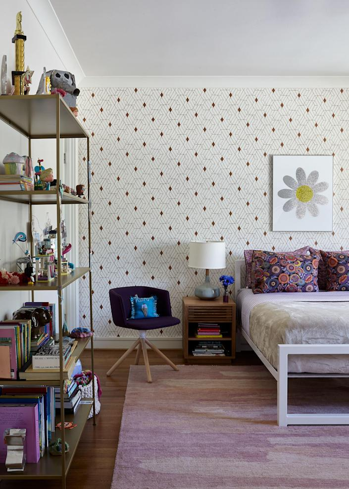 """In this bedroom, decorated for the couple's preteen daughter, a patterned wallpaper from <a href=""""https://www.hyggeandwest.com/products/quilt-copper"""" rel=""""nofollow noopener"""" target=""""_blank"""" data-ylk=""""slk:Hygge & West"""" class=""""link rapid-noclick-resp"""">Hygge & West</a> with copper hues is softened by a pale pink rug from <a href=""""http://josephcarinicarpets.com"""" rel=""""nofollow noopener"""" target=""""_blank"""" data-ylk=""""slk:Joseph Carini Carpets"""" class=""""link rapid-noclick-resp"""">Joseph Carini Carpets</a>. The white iron bed is from Room & Board."""