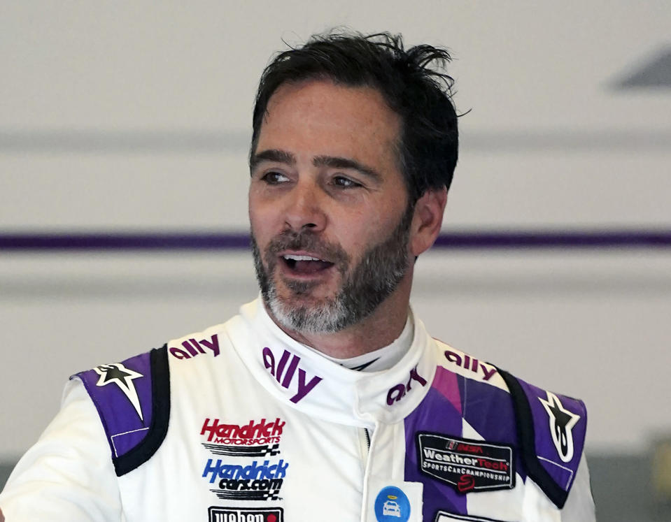 FILE - In this Jan. 23, 2021, file photo, Jimmie Johnson interacts with crew members in his garage during a practice session for the Rolex 24 hour auto race at Daytona International Speedway in Daytona Beach, Fla. The Associated Press asked eight of the greatest current and former champions, including Johnson, from seven different sports to find out what impressed them most about Tom Brady.(AP Photo/John Raoux, File)