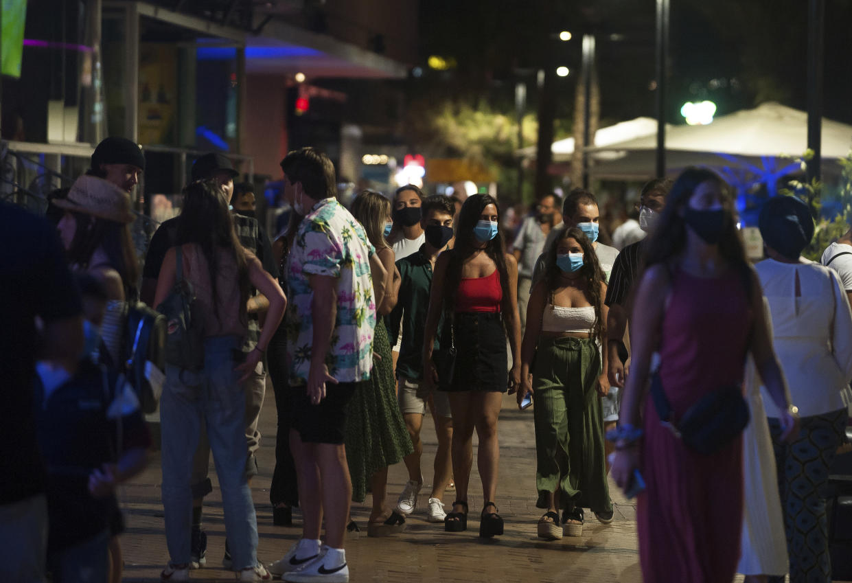 A group of people wearing face masks walk on the street In Fuengirola, near Malaga, Spain, Saturday, Aug. 8, 2020. The increase in Spain of coronavirus outbreaks associated with nightlife has set off alarms in recent days, mainly in tourist areas where pubs and discos are full before the summer tourist campaign. (AP Photo/Jesus Merida)