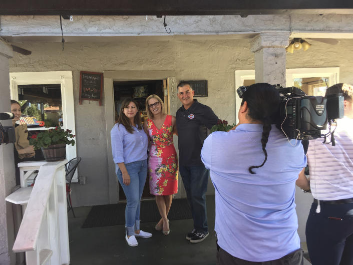U.S. Senate candidate and Democratic Rep. Kyrsten Sinema poses in between America Corrales and Terry Bortin in front of media on Tuesday, Nov. 6, 2018, at the couple's taco restaurant in Phoenix. Sinema, who is locked in a tight race with Republican Rep. Martha McSally is spending the final hours of election day talking to voters. (AP Photo/Terry Tang)