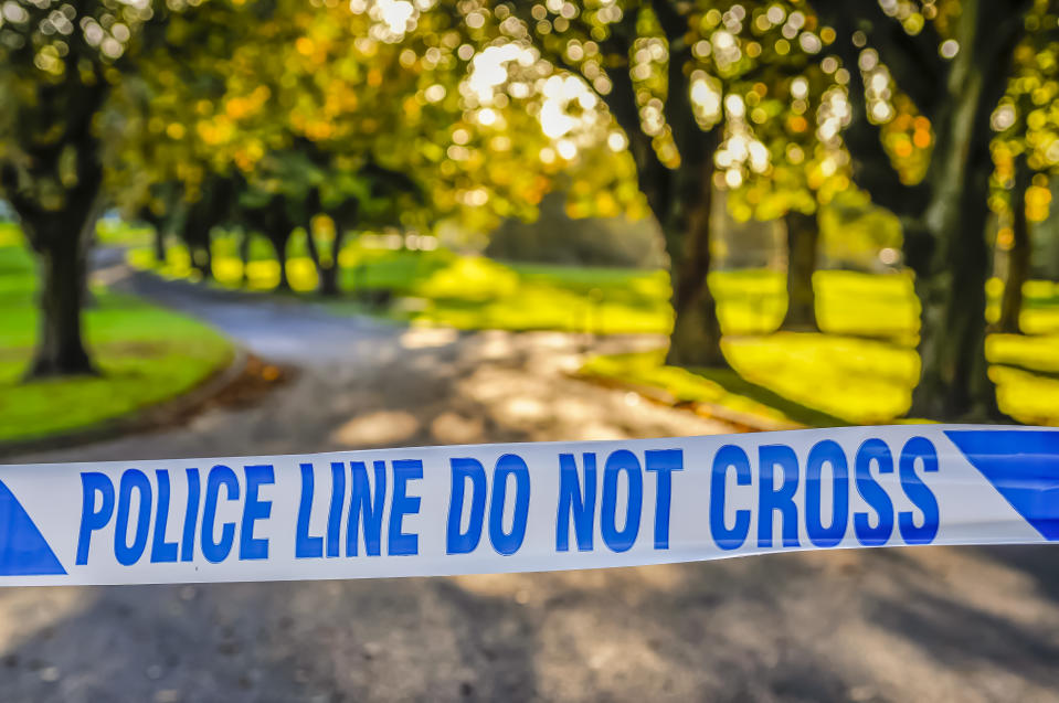 Police tape stretched across the entrance to a park following a murder