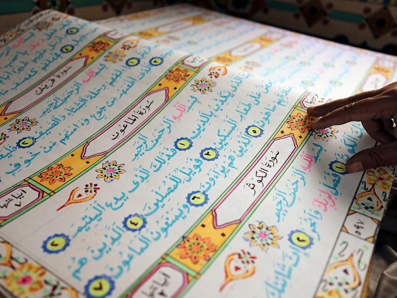 Saad Mohammed reads from another Quran that he has handwritten (Reuters)