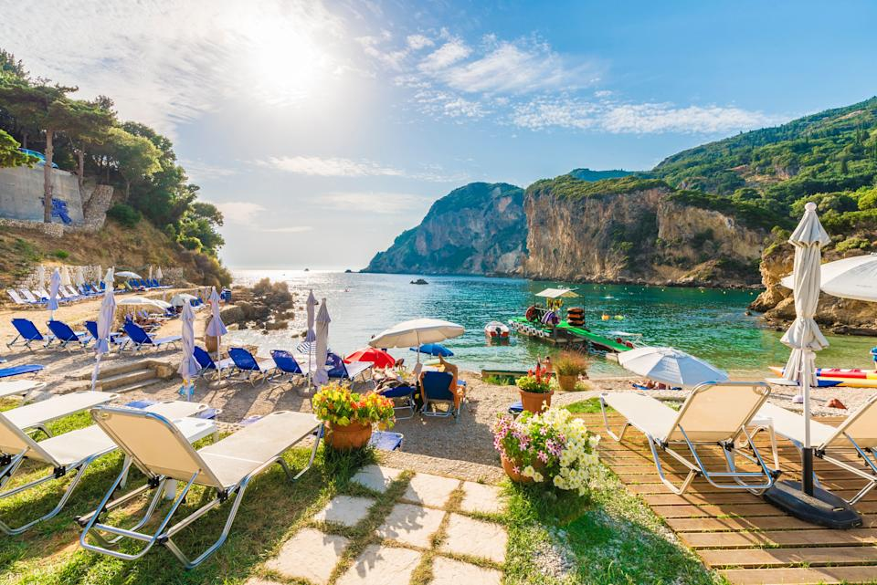 Sunbeds and umbrella on the beach in Corfu Island, Greece. (Photo: Balate Dorin via Getty Images)