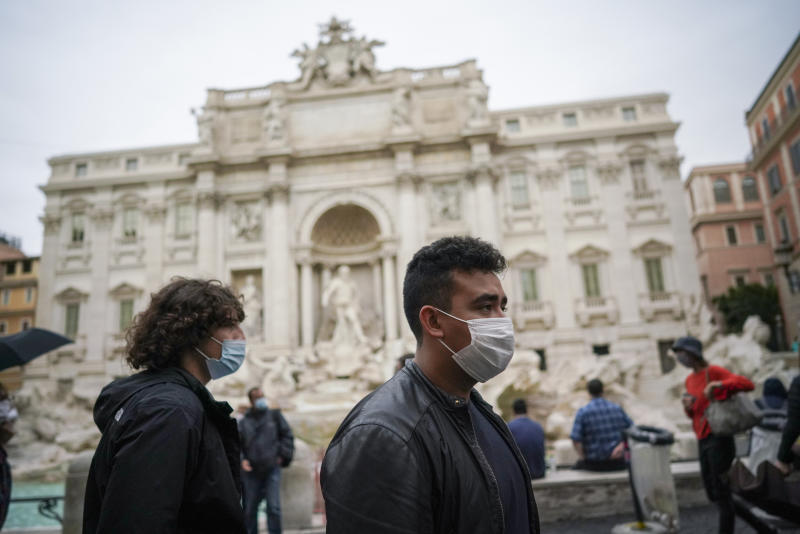 People wear face masks to prevent the spread of COVID-19 as they walk past the Trevi Fountain, in Rome, Saturday, Oct. 3, 2020. As of Saturday it is mandatory to wear masks outdoors in Lazio, the region that includes Rome. (AP Photo/Andrew Medichini)