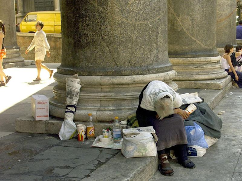 An elderly homeless person rests in the shadow of the Pantheon, central Rome (Getty)