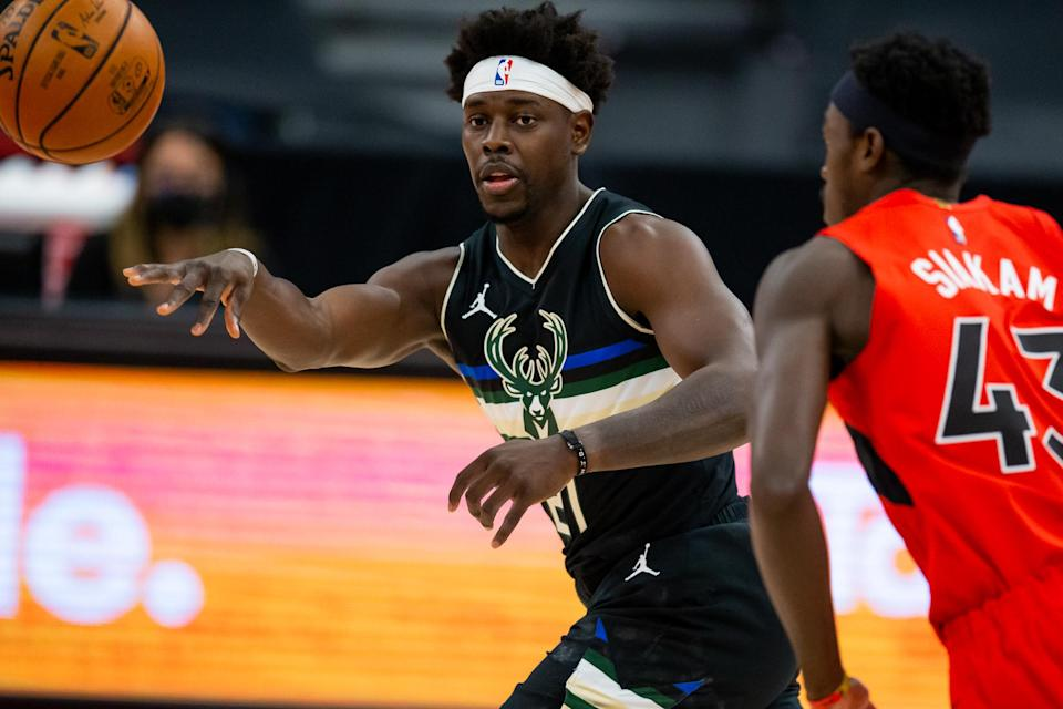 Jan 27, 2021; Tampa, Florida, USA; Milwaukee Bucks guard Jrue Holiday (21) passes during the first quarter of a game against the Toronto Raptors at Amalie Arena.