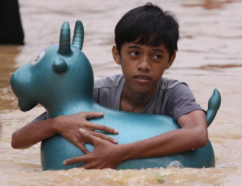 A boy uses a plastic toy as a floater as he wades along a flooded road in Marikina, east of Manila, Philippines on Thursday Aug. 9, 2012. A fresh deluge forced more evacuations along fast-rising rivers in the Philippine capital Thursday, as the city and surrounding areas struggled to deal with widespread flooding triggered by nearly two weeks of relentless rains. (AP Photo/Aaron Favila)