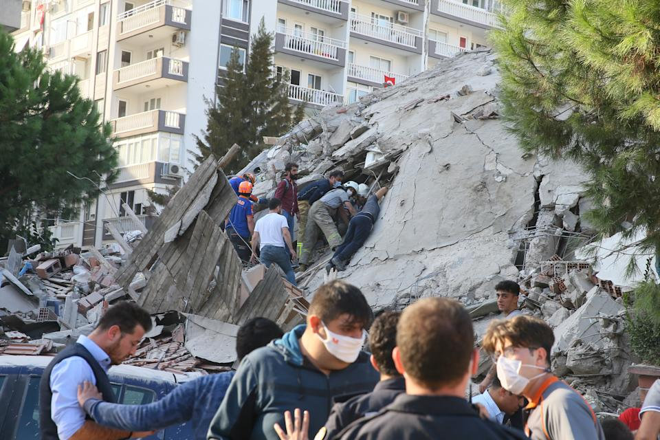 IZMIR, TURKEY - OCTOBER 30: Wounded people are cut free from the wreckage as search and rescue works continue at debris of a building in Bayrakli district after a magnitude 6.6 quake shook Turkey's Aegean Sea coast, in Izmir, Turkey on October 30, 2020. (Photo by Mehmet Emin Menguarslan/Anadolu Agency via Getty Images)