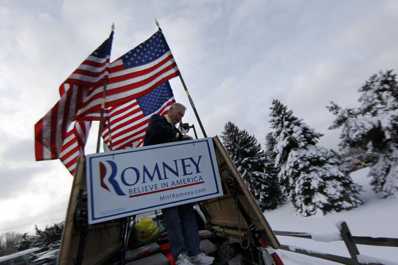 Jim Wilson, a supporter of Republican presidential candidate, former Massachusetts Gov. Mitt Romney, lashes American flags to the back of his pickup truck before Romney speaks at the Ingham Lincoln Day Breakfast in Lansing, Mich., Saturday, Feb. 25, 2012. (AP Photo/Gerald Herbert)