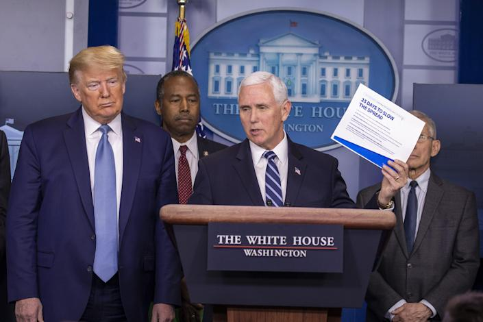 President Donald Trump listens to Vice President Mike Pence speak during a briefing at the White House on March 21, 2020.