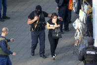 "Georgian police officers escorts a woman who escaped from a bank where an armed assailant has taken several people hostage, in the town of Zugdidi in western Georgia, Wednesday, Oct. 21, 2020. The Georgian Interior Ministry didn't immediately say how many people have been taken hostage in the town of Zugdidi in western Georgia, or what demands the assailant has made. Police sealed off the area and launched an operation ""to neutralize the assailant,"" the ministry said in a statement. (AP Photo/Zurab Tsertsvadze)"