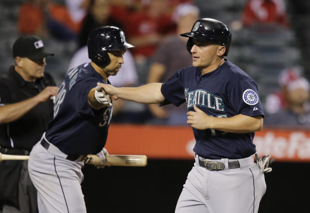 Seattle Mariners' Kyle Seager, right, is greeted by teammate Raul Ibanez after he scored on a single by Kendrys Morales during the 10th inning of a baseball game against the Los Angeles Angels in Anaheim, Calif., Tuesday, June 18, 2013. (AP Photo/Jae C. Hong)