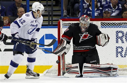Carolina Hurricanes goalie Dan Ellis, right, makes a save on a deflection by Tampa Bay Lightning's Dana Tyrell during the first period of an NHL hockey game, Sunday, April 21, 2013, in Tampa, Fla. (AP Photo/Mike Carlson)