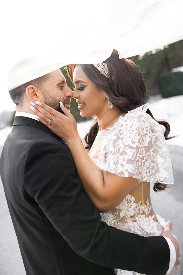 A bride and groom press their noses together as the brides's veil flows over their heads
