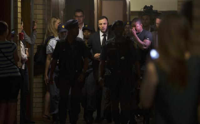 """South African Olympic and Paralympic track star Oscar Pistorius (C) arrives at the North Gauteng High Court in Pretoria, September 12, 2014. Pistorius returned to court on Friday after being cleared of murdering girlfriend Reeva Steenkamp, but the South African Olympic and Paralympic sprinter could still be convicted of culpable homicide for the """"negligent"""" shooting of the model. REUTERS/Rogan Ward (SOUTH AFRICA - Tags: SPORT ATHLETICS CRIME LAW)"""
