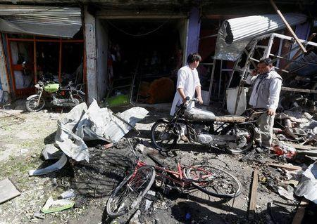 Afghan shopkeepers collect reamains in front of a shop after a suicide attack in Kabul, Afghanistan. July 24, 2017.REUTERS/Omar Sobhani