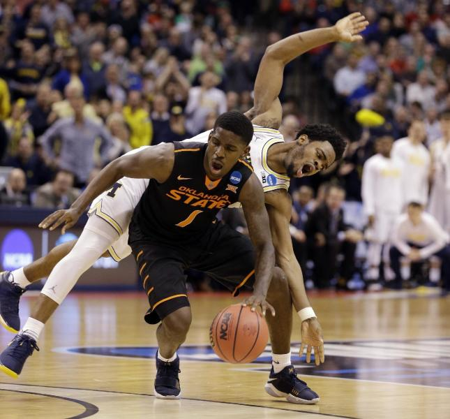Michigan guard Derrick Walton Jr. (10) fouls Oklahoma State guard Jawun Evans (1) from behind during the second half of a first-round game in the men's NCAA college basketball tournament in Indianapolis, Friday, March 17, 2017. Michigan defeated Oklahoma State 92-91. (AP Photo/Michael Conroy)