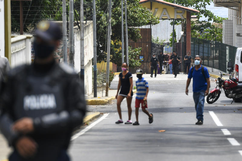 Security forces, back, leave a facility in the Macuto area in La Guiara, Venezuela, Sunday, May 3, 2020. Interior Nestor Reverol said on state television that Venezuelan forces overcame an armed maritime incursion by boats through the port city of La Guaira from neighboring Colombia before dawn Sunday, in which several attackers were killed and others detained. (AP Photo/Matias Delacroix)