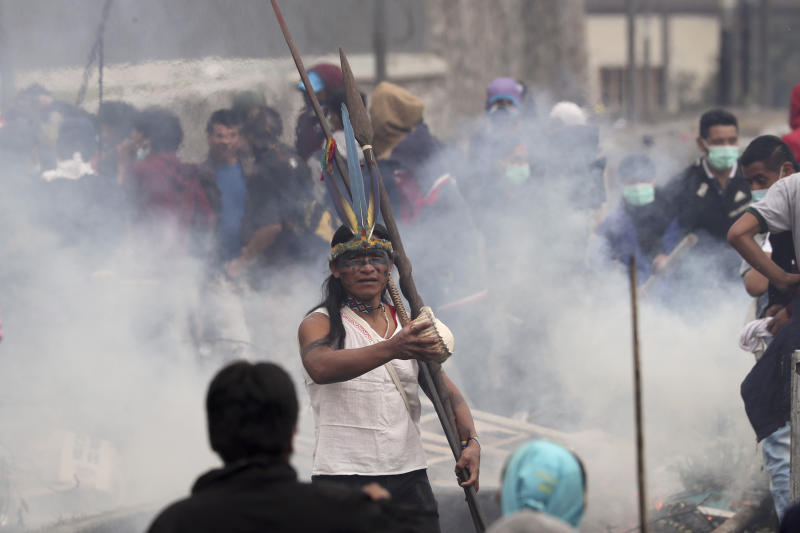 Anti-government demonstrator stands in the middle of tear gas during clashes with police in Quito, Ecuador, Friday, Oct. 11, 2019. Protests, which began when President Lenin Moreno's decision to cut subsidies led to a sharp increase in fuel prices, have persisted for days. (AP Photo/Dolores Ochoa)