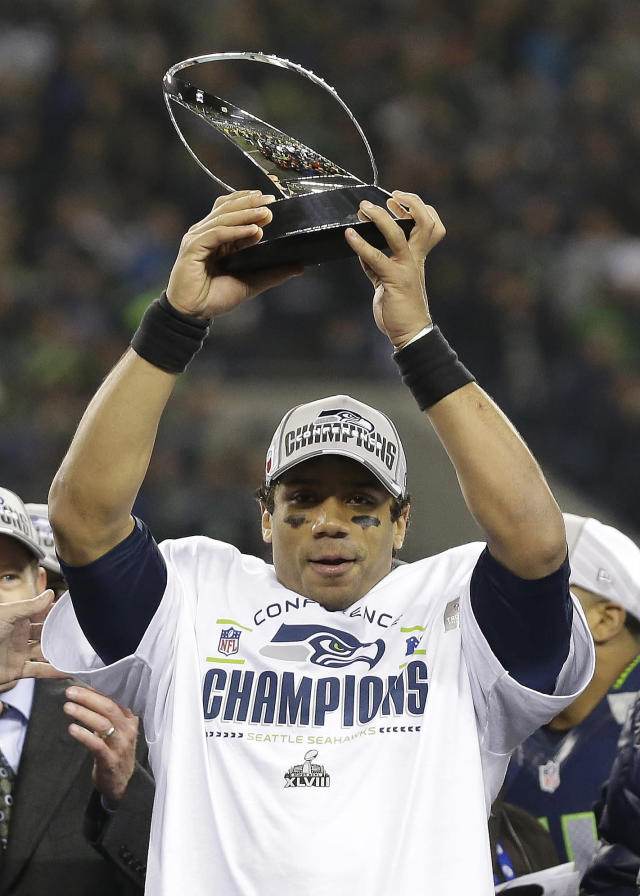 Seattle Seahawks' Russell Wilson holds up the George Halas Trophy after the NFL football NFC Championship game against the San Francisco 49ers Sunday, Jan. 19, 2014, in Seattle. The Seahawks won 23-17 to advance to Super Bowl XLVIII. (AP Photo/Elaine Thompson)