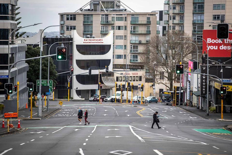 People cross nearly empty streets in the central business district of Auckland, New Zealand. Source: AP