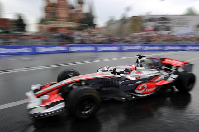"""Formula One Vodafone McLaren Mercedes team driver Jenson Button of Britain drives past St. Basils cathedral during the """"Moscow City Racing"""" show on July 17, 2011 in central Moscow. AFP PHOTO / NATALIA KOLESNIKOVA (Photo credit should read NATALIA KOLESNIKOVA/AFP/Getty Images)"""