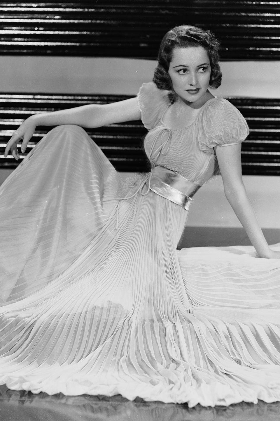 <p>The British-born actress dons a pleated dress with a metallic belt and puff sleeves. </p>