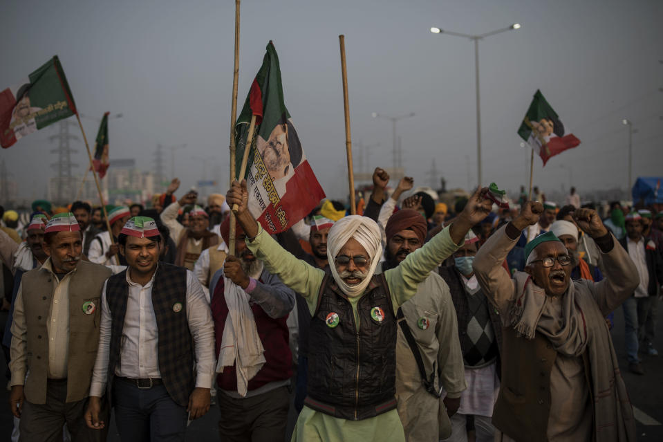 Indian farmers shout slogans as they block a major highway during a protest against new farm laws at the Delhi-Uttar Pradesh state border, India, on Dec. 5, 2020. India's prime minister Narendra Modi Friday held virtual talks with farmers from six states and asked them to explain how the government's agricultural policies have benefited them, a month after facing massive farmer protests that have rattled his administration. (AP Photo/Altaf Qadri)