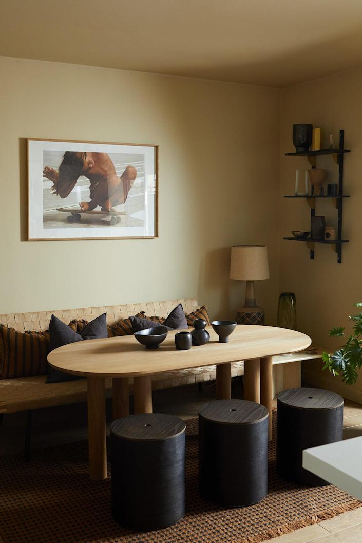 In the open plan kitchen–dining room, bathed in natural light, the stools and table are custom-made by Fred Rigby Studio and complemented by an Ilse Crawford for IKEA Sinnerlig daybed bought in 2015. Above the table is a photograph by Hugh Holland and on the wall in the corner are Sector Shelves from Ferm Living.