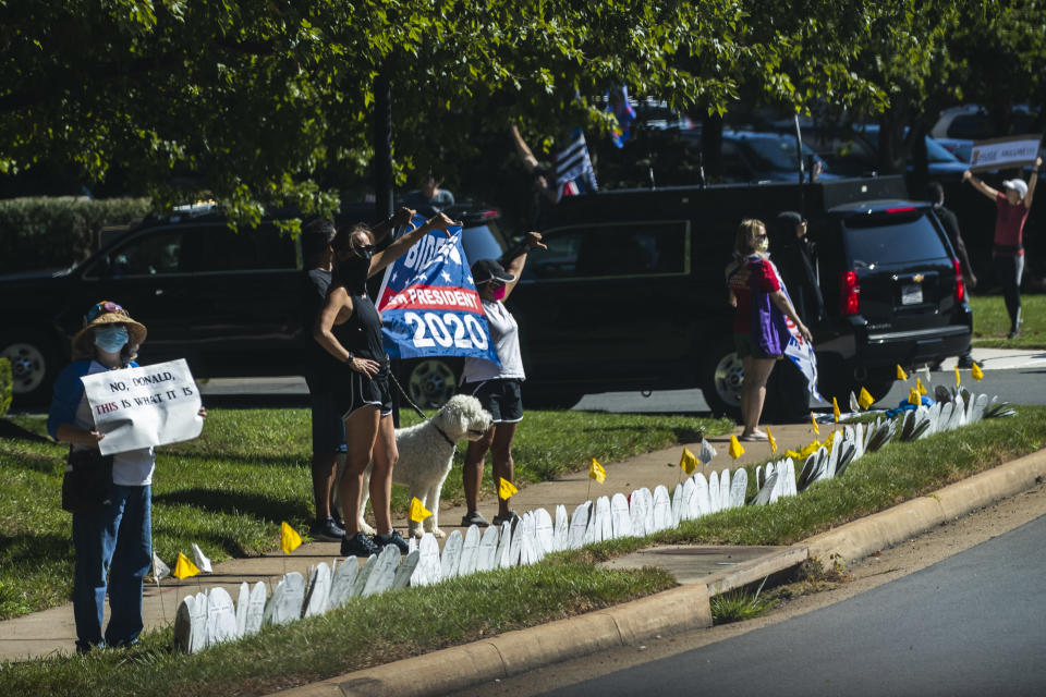 Supporters of President Donald Trump and protesters hold banners as the motorcade of President Trump enters the Trump National Golf Club in Sterling, Va., Sunday, Aug. 30, 2020. (AP Photo/Manuel Balce Ceneta)