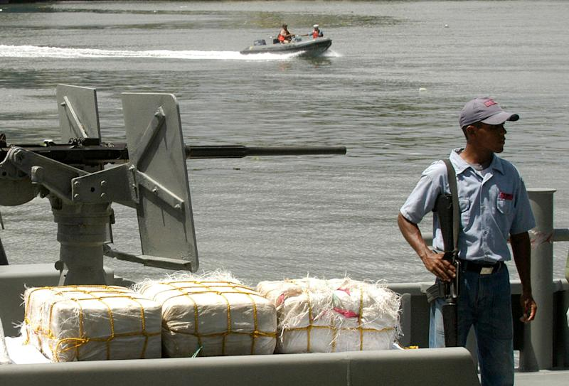 FILE - In this June 25, 2007 file photo, a Dominican Navy soldier stands guard over bales of cocaine during a news conference in Santo Domingo, Dominican Republic. Authorities in the Dominican Republic seized 9 tons of cocaine in 2012, the third consecutive record, according to the country's national drug control agency. In January alone, they seized another 3 tons off the country's southern coast. (AP Photo/Jorge Cruz, File)