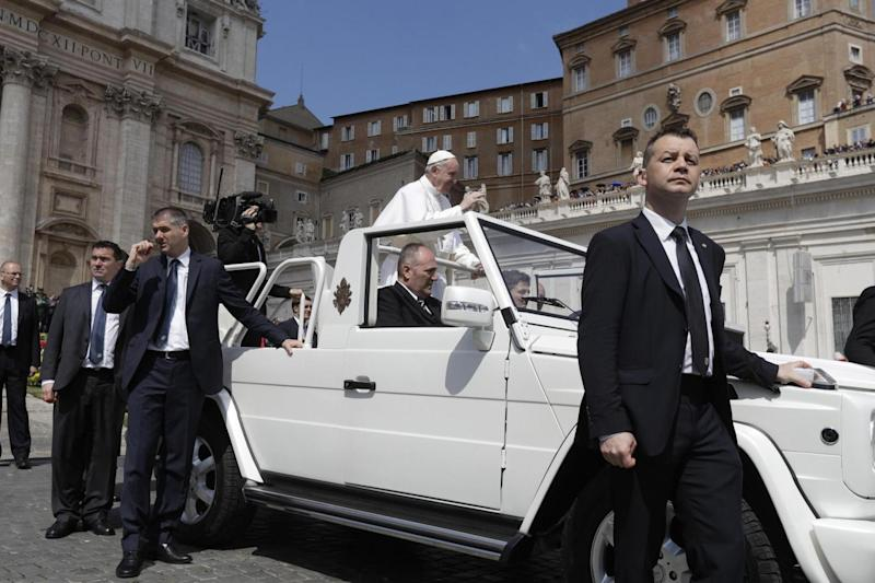 Security: Pope Francis protected by his bodyguards as he is driven through the crowd after celebrating Easter Sunday Mass. (AP)