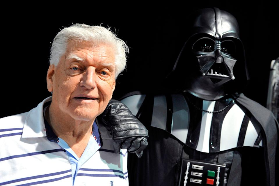 "David Prowse, seen here in 2013 with a costumed Darth Vader at a ""Star Wars"" convention in France, has died at age 85. The British actor was the man behind the menacing black mask of the ""Star Wars"" villain in the original trilogy."