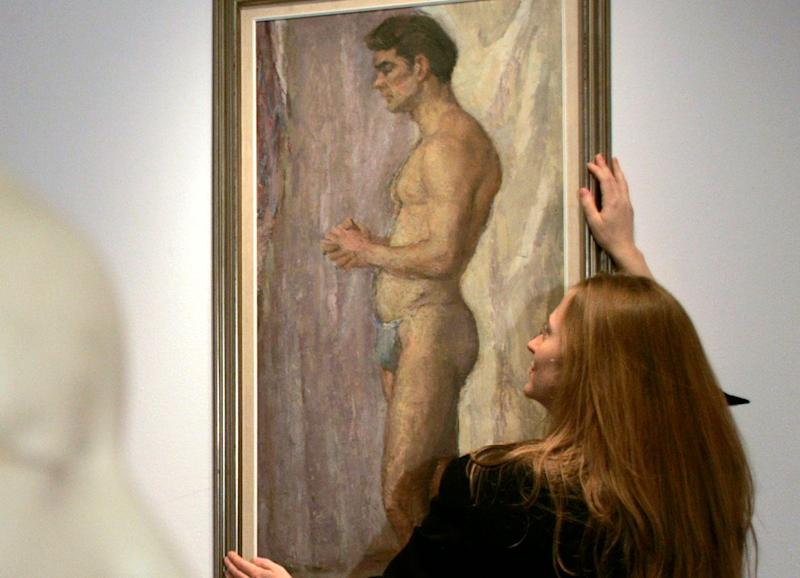 A gallery assistant looks at a 1952 oil on canvas painting of Scottish actor Sean Connery in the Edinburgh College of Art in Scotland on Oct. 25, 2007. Al Fairweather, a student, painted it just before Connery auditioned for the stage production of South Pacific. (Photo: David Moir / Reuters)