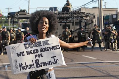 CLICK IMAGE for slideshow: A protester shouts as she moves away from a line of riot police in Ferguson, Mo. on Wednesday, Aug. 13, 2014. On Saturday, Aug. 9, 2014, a white police officer fatally shot Michael Brown, an unarmed black teenager, in the St. Louis suburb. (AP Photo/St. Louis Post-Dispatch, J.B. Forbes)